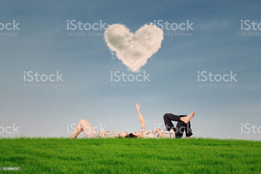 Couple enjoy holiday under heart cloud in park stock photo