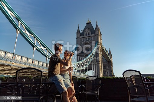 Couple enjoy sunset with beer and water sittin on a table. Tower bridge on the back
