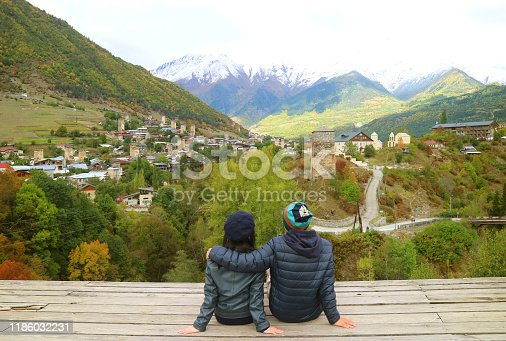 872969580istockphoto Couple Enjoy the Breathtaking View of Mestia Town with Svan Tower in the Early Autumn, Svaneti Region, Archaeological site in Georgia 1186032231