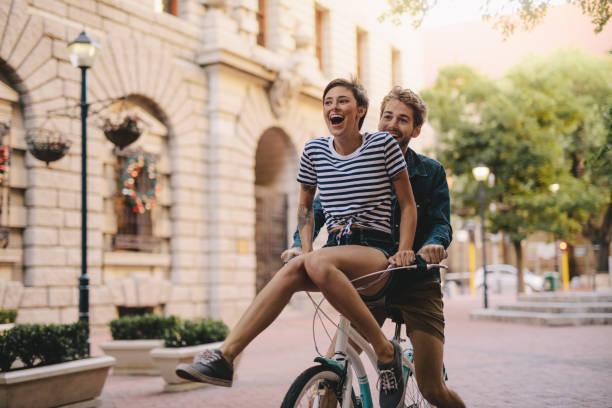 paar genießt ein fahrrad fahren in der stadt - junges paar stock-fotos und bilder
