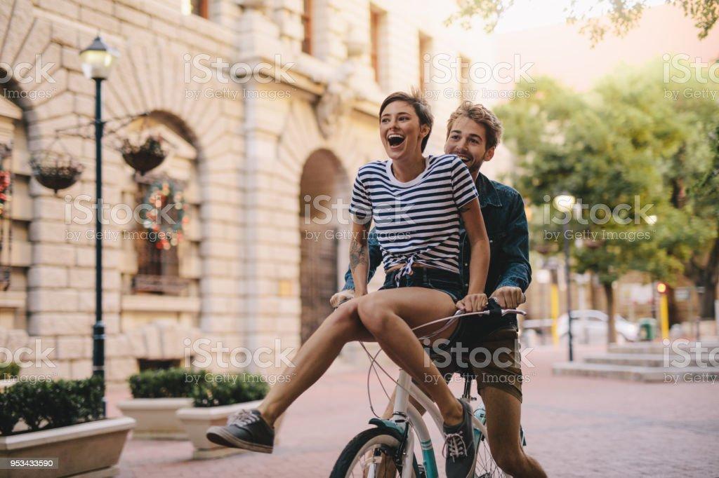 Casal, desfrutando de uma bicicleta andar na cidade - foto de acervo