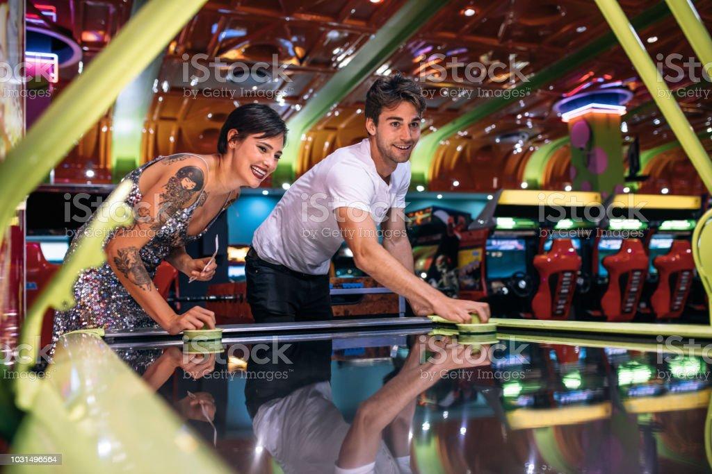 Casal, desfrutando de um jogo de hóquei de ar em uma fliperama de jogos - foto de acervo