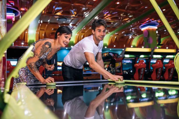 paar genießt eine airhockey bei einem gaming-arcade-spiel - arkade stock-fotos und bilder
