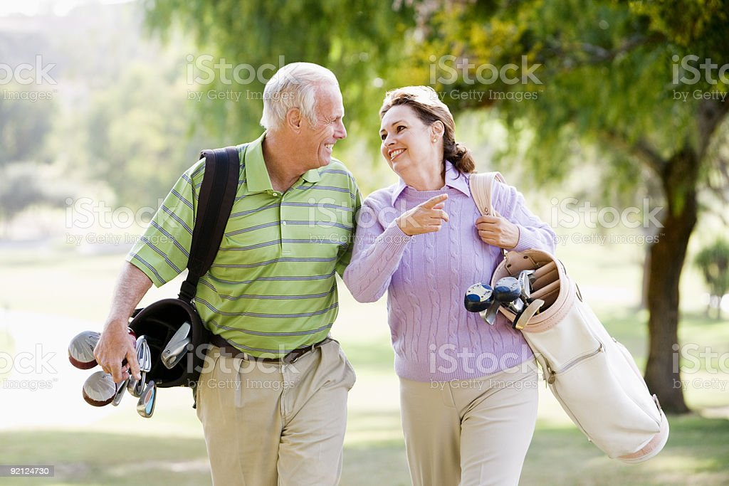 Couple Enjoying A Game Of Golf Couple Enjoying A Game Of Golf and smiling 50-59 Years Stock Photo