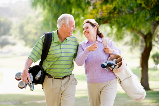 Couple Enjoying A Game Of Golf Stock Photo - Download Image Now