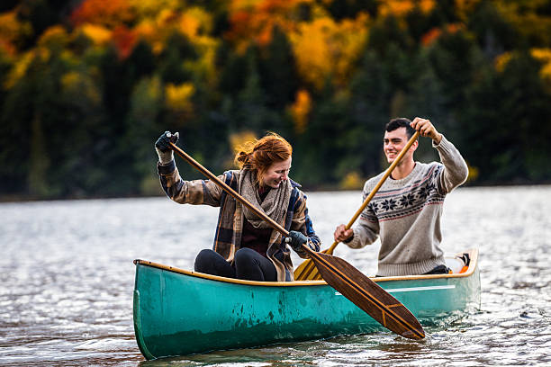 couple enjoying a ride on a typical canoe in canada - voyages au canada photos et images de collection
