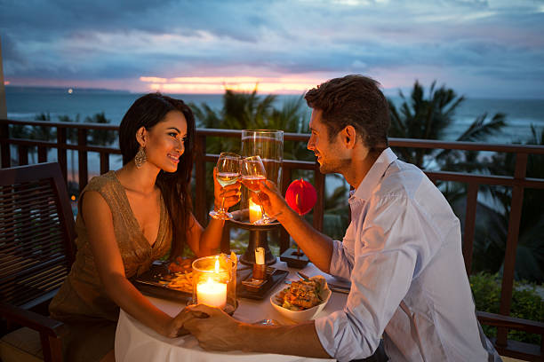 couple enjoying a romantic dinner by candlelight young couple enjoying a romantic dinner by candlelight, outdoor date night romance stock pictures, royalty-free photos & images
