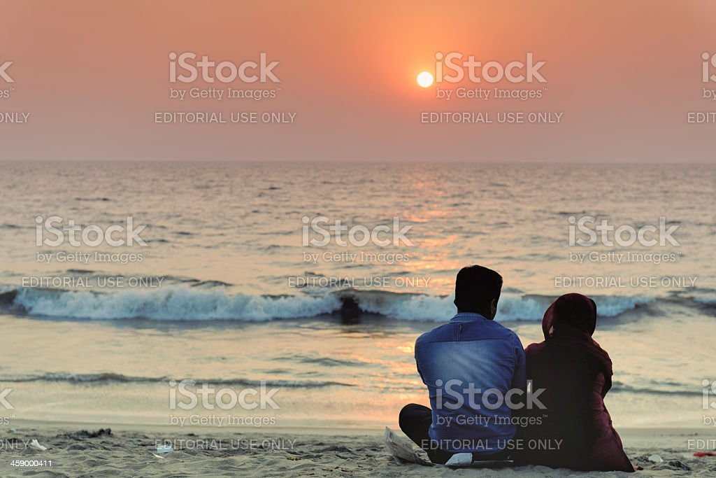 Couple enjoying a romantic sunset on the beach stock photo