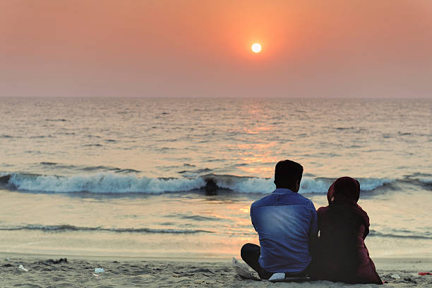Couple enjoying a romantic sunset on the beach Kozhikode, Kerala,India - January 16 , 2013: Couple sitting on the Calicut Beach and enjoying a beautiful sunset. Kozhikode, formerly known as Calicut, is a city on the Malabar coast in southern India. romance stock pictures, royalty-free photos & images