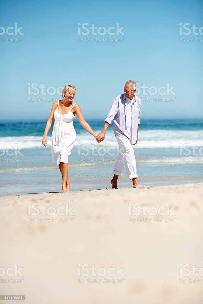 Couple enjoying a walk on the beach royalty-free stock photo