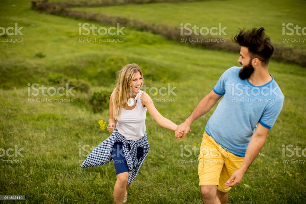 Couple enjoying a walk through grass land royalty-free stock photo