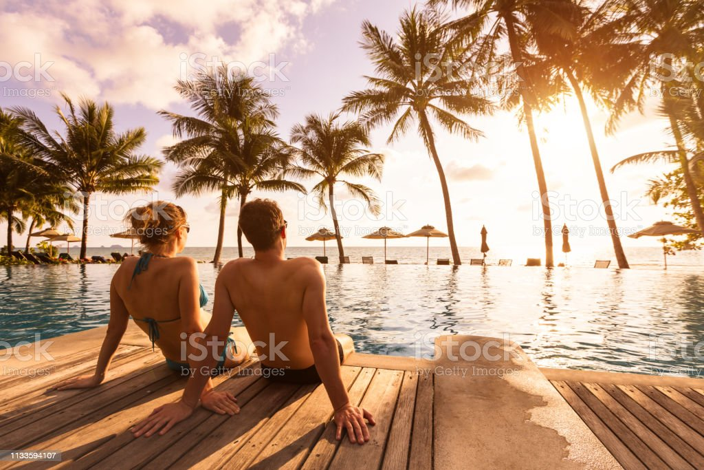 Couple enjoying beach vacation holidays at tropical resort with swimming pool and coconut palm trees near the coast with beautiful landscape at sunset, honeymoon destination royalty-free stock photo