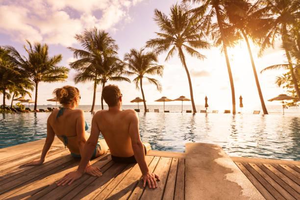 pareja disfrutando de vacaciones en la playa en el complejo tropical con piscina y palmeras de coco cerca de la costa con hermoso paisaje al atardecer, destino de luna de miel - playa fotografías e imágenes de stock