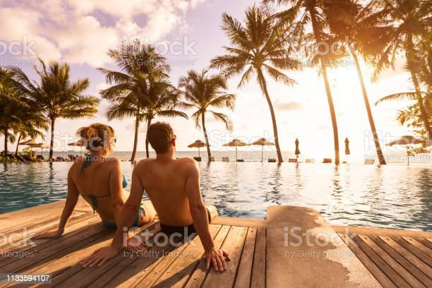 Photo of Couple enjoying beach vacation holidays at tropical resort with swimming pool and coconut palm trees near the coast with beautiful landscape at sunset, honeymoon destination
