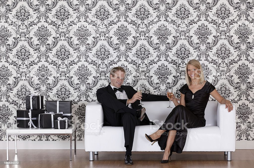 Couple enjoying champagne on a couch royalty-free stock photo