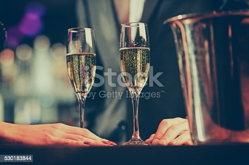 close up shot of couple enjoying champagne  in a night club