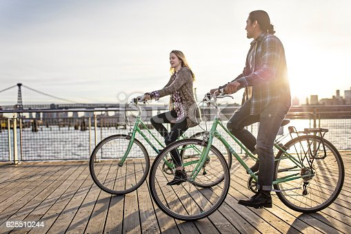 Shot of young couple riding bikes on promenade in evening
