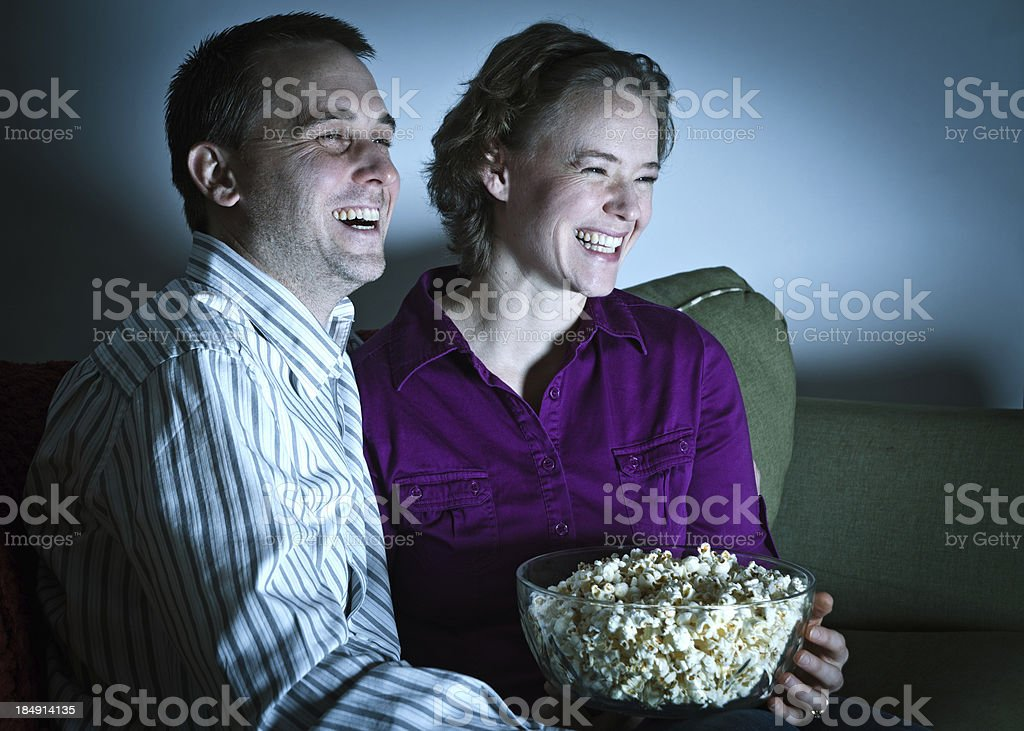 Couple enjoying date night in, watching a movie stock photo