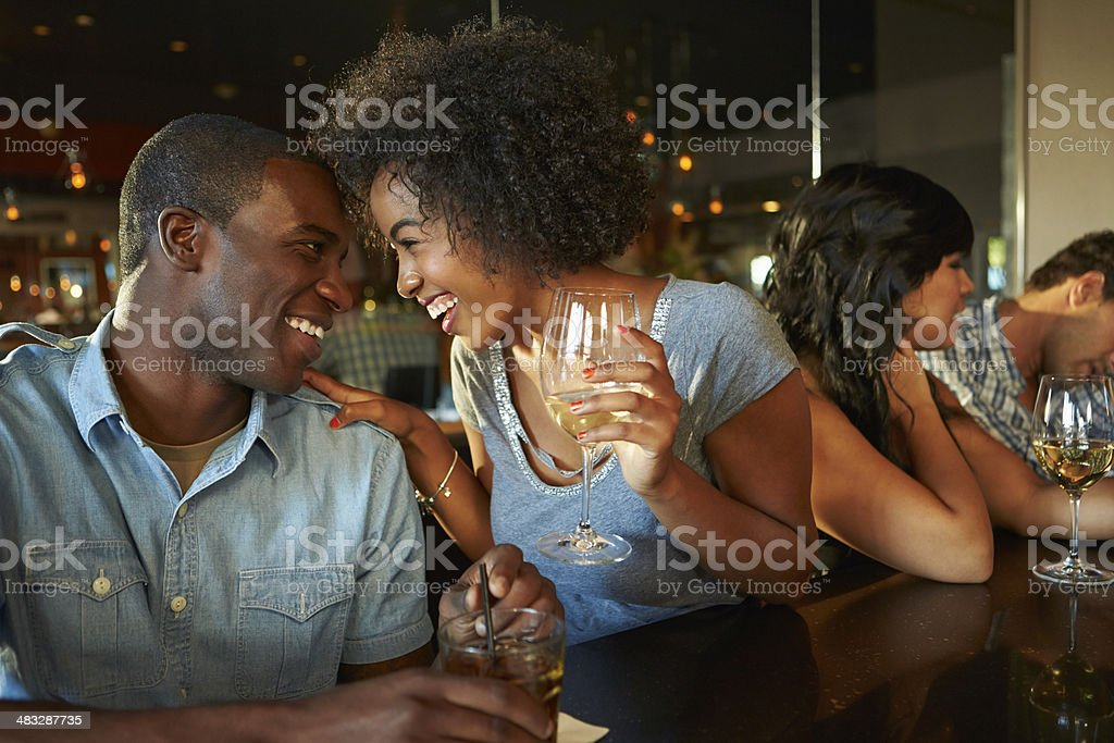 Couple Enjoying Drink At Bar With Friends stock photo