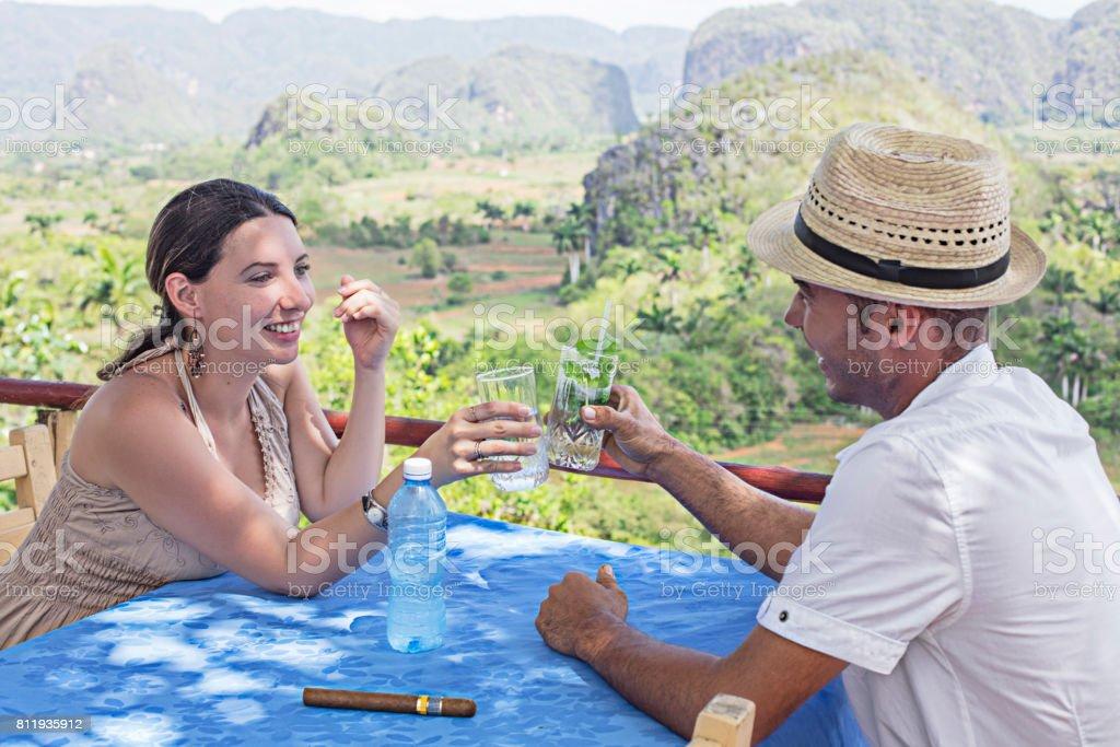 Couple enjoying drinks against Valle De Vinales stock photo