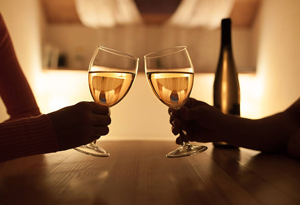 Couple enjoying evening drink Couple enjoying glass of white wine at home. table for two stock pictures, royalty-free photos & images