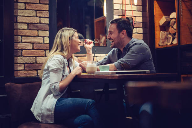 couple enjoying evening drinks in bar - date night stock pictures, royalty-free photos & images