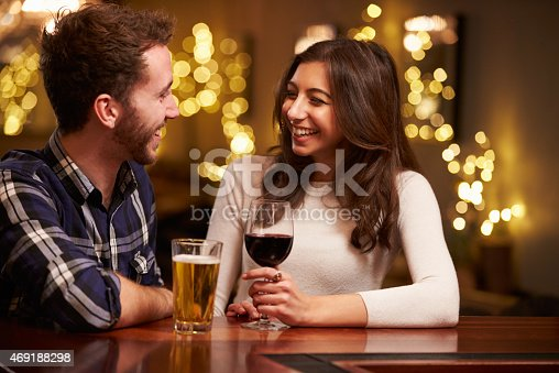 istock Couple Enjoying Evening Drinks In Bar 469188298