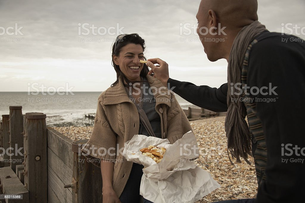 Couple enjoying fish 'n' chips on the beach royalty-free stock photo