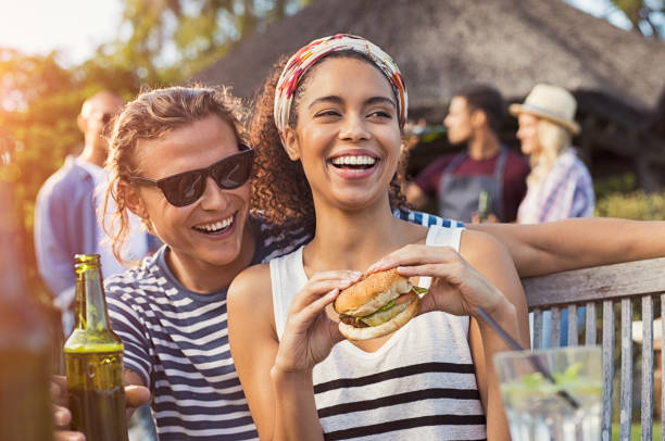 Couple enjoying food and drinks at party stock photo
