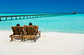 Couple enjoying holidays sitting on lounge chairs at tropical paradise beach at Dhiffushi Holiday island at South Ari atoll, Maldives. Beautiful turquoise Indian ocean sea with white sand. Luxury travel holidays background. Model and Property released.