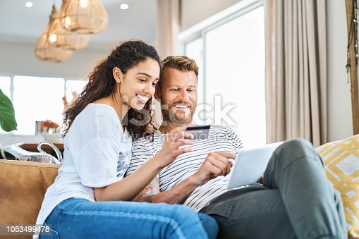 Woman sitting with credit card by man paying through electronic banking. Smiling multi-ethnic couple is enjoying shopping through digital tablet. They are in living room at home.