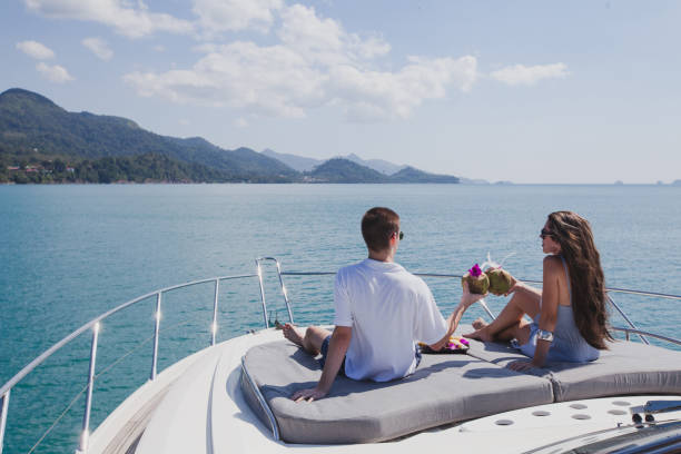 couple enjoying honeymoon onboard of luxury boat, luxurious yacht couple enjoying honeymoon onboard of luxury boat, luxurious yacht in tropical sea, man and woman drinking coconuts and relax military private stock pictures, royalty-free photos & images