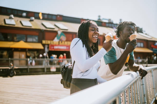 Couple Enjoying Ice Cream on Seattle Pier A cute young man and woman enjoy a tasty ice cream waffle cone on a sunny day in downtown Seattle. haitian ethnicity stock pictures, royalty-free photos & images