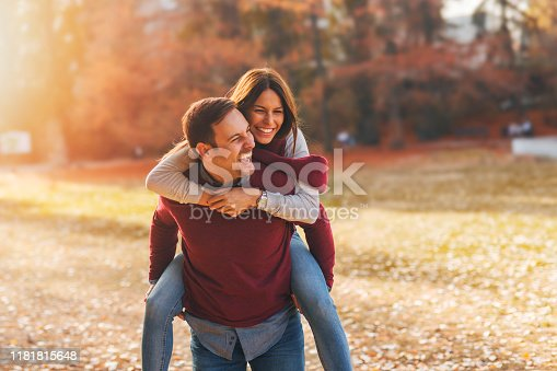 Romantic love couple smiling and playing at public part in autumn.