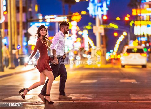 A couple holding hands as they run across the street at a crosswalk in Las Vegas at night.