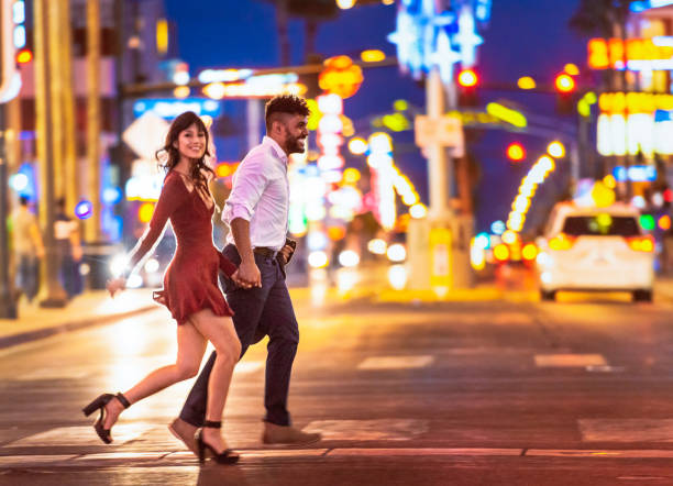 Couple enjoying Las  Vegas nightlife A couple holding hands as they run across the street at a crosswalk in Las Vegas at night. nightlife stock pictures, royalty-free photos & images