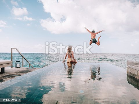 Couple enjoying tropical vacations from the edge of an infinity pool in private over water villa. People travel luxury holidays