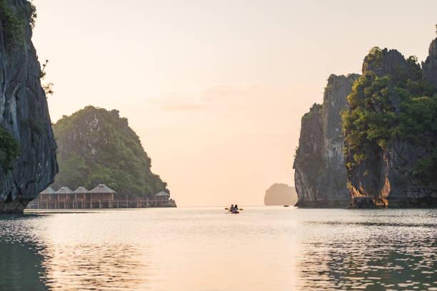Couple Enjoying Morning Kayak, Surrounded by Karst Formations, North Vietnam stock photo