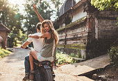 Rear view shot of young couple enjoying motorcycle ride on village road. Beautiful young woman sitting on back with her arm raised.