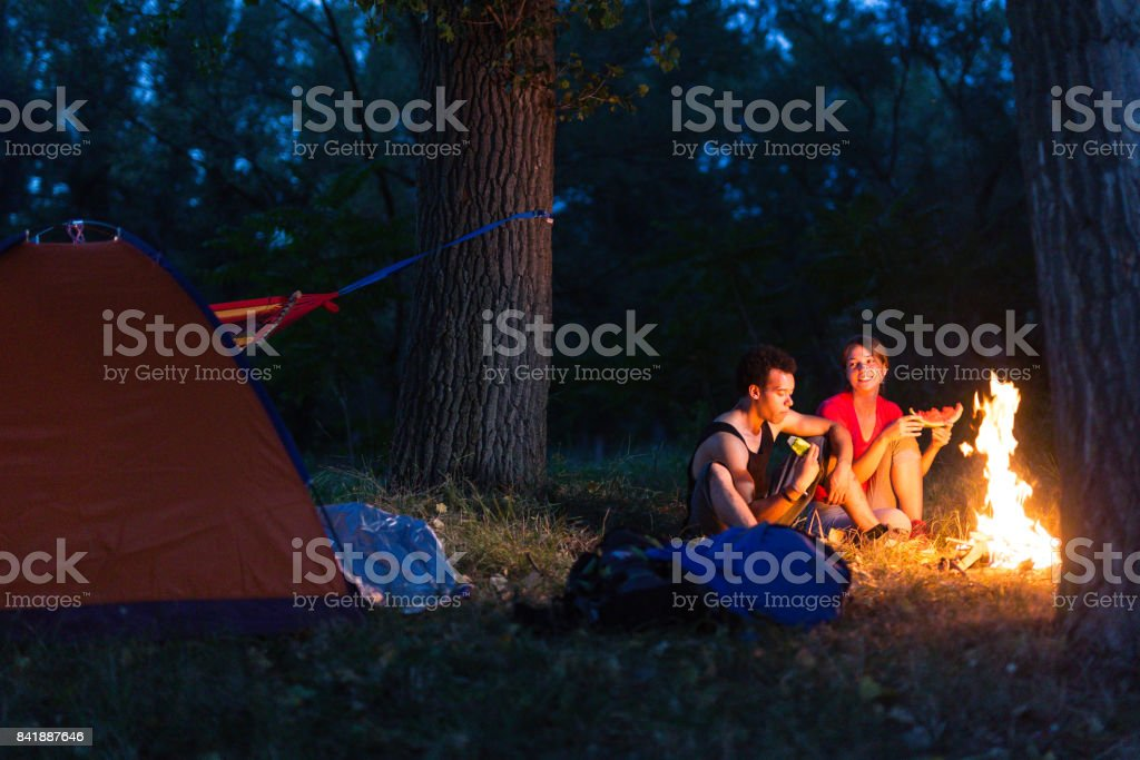 Couple enjoying next to the campfire stock photo