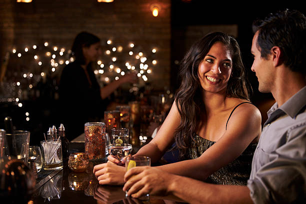 Couple Enjoying Night Out At Cocktail Bar Couple Enjoying Night Out At Cocktail Bar date night romance stock pictures, royalty-free photos & images