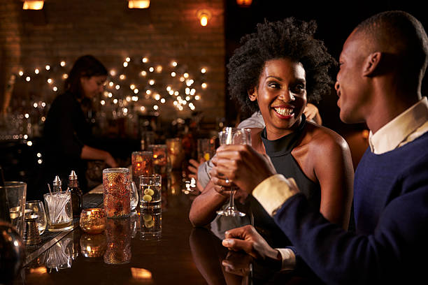 couple enjoying night out at cocktail bar - couple lap stock photos and pictures