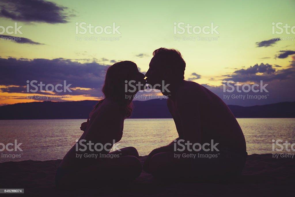 Couple enjoying on the beach in sunset / sunrise time. stock photo