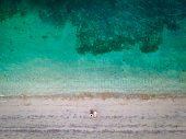 Couple enjoying and relaxing on the beach sitting on the tanning chairs at sunset top down aerial view with copy space