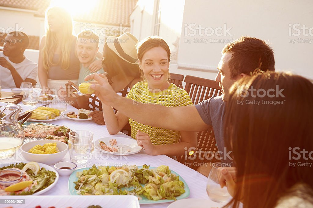 Couple Enjoying Outdoor Summer Meal With Friends stock photo