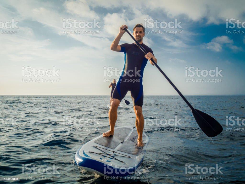 Couple enjoying paddleboarding stock photo