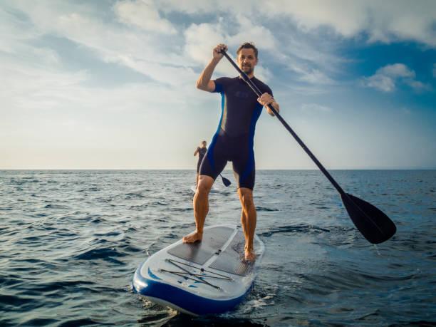 paar genießt paddling - stehpaddeln stock-fotos und bilder