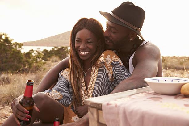 couple enjoying picnic on cliffs by sea - schwarze romantik stock-fotos und bilder