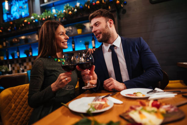 Couple enjoying red wine on Valentine's Day Couple enjoying red wine on Valentine's Day table for two stock pictures, royalty-free photos & images