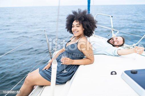 Couple drinking wine on yacht, enjoying summer vacations.
